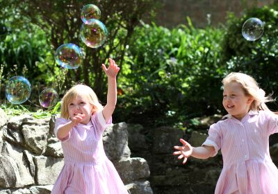 Pre-school girls playing with bubbles at Nursery in Southsea, Hampshire