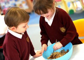 Nursery School mixing the liquid chocolate