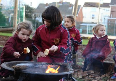 Independent School Portsmouth Girls sitting outside toasting some food over a small fire