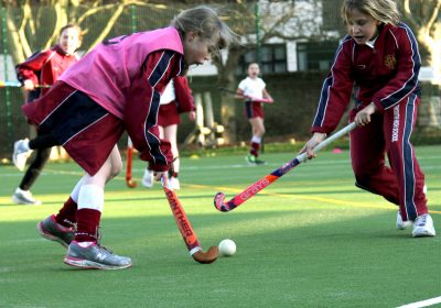 Girls playing hockey on astroturf at Private School Portsmouth