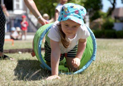 Pre-School girl scrambling through a hoop