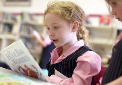 Reception Class reading in a library lesson