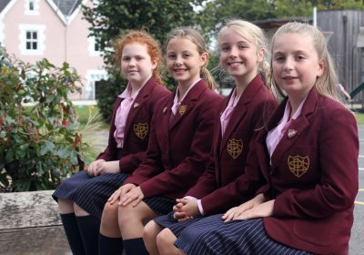 Four Head Girls sitting outside on a bench at Portsmouth High Prep School