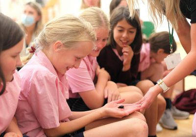 girls holding a cockroach